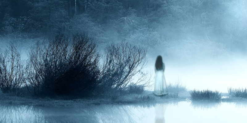 Scary woman's ghost standing in a old creepiest lake.